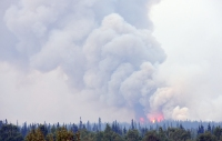 Smoke rolls off the flats east of Chalkyitsik as firefighters burnout around a cabin site Friday evening, July 20, 2019. Assisted by a drone dropping ping-pong like plastic balls that ignite, crews were preparing for a future firing operation that will remove a large stand of black spruce ahead of the Bearnose Hill Fire (#407). Sam Harrel/Alaska Interagency Incident Management Team