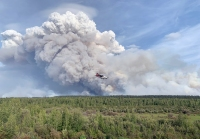 Jump-12, an Alaska Smokejumper Casa, makes it final approach to Chalkytsik, Alaska, as a plume rises from burnout operations on the Bearnose Hill Fire (#407) on Sunday afternoon, July 21, 2019. The aircraft was delivering personnel to the Chalkyitsik Complex. Ed Sanford/Alaska Interagency Incident Management Team