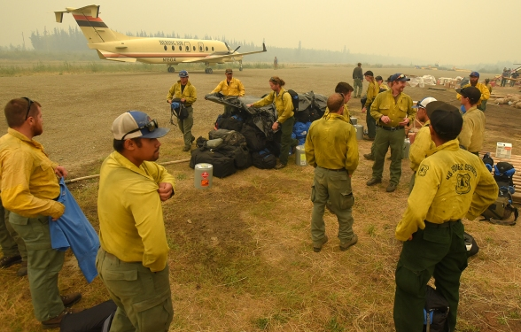 The Winema Hotshots of Oregon cover the pile of their personal gear bags as a thunderstorm moves in after they arrived at the Chalkyitsik Airport on Thursday, July 25, 2019.