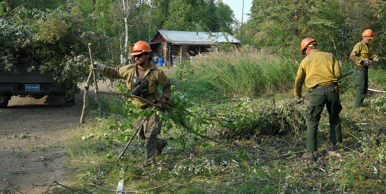 Photo of Members of the North Star Type 2 hand crew pick up brush piles in the village of Chalkyitsik, Alaska, on Saturday, July 13, 2019. Firefighters have completed their structure protection setup in the community of 57 residents. The Frozen Calf Fire (#367) and the Bearnose Hill Fire (#407) continue to grow toward the village. Sam Harrel/Alaska Interagency Incident Management Team
