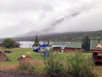 A helicopter contracted by the Alaska Division of Forestry sits near Rainy Pass Lodge on Wednesday morning, July 24, 2019 as smoke from the Rainy Pass Fire a mile away is visible. Photo by Greg King/Soloy Helicopters