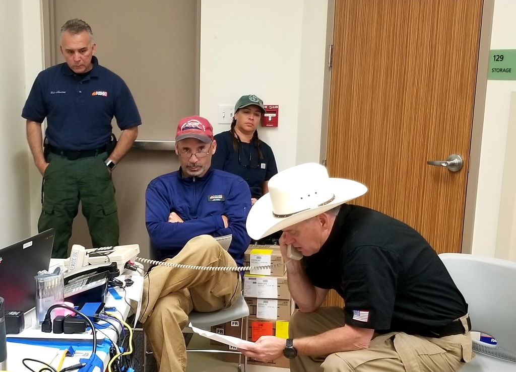 Four members of the Cornucopia Complex incident management team sit around a table listening to radio and telephone reports from fire crews in the field.