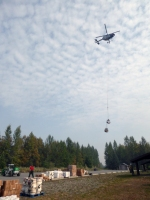 A helicopter transports a sling load of supplies to firefighters working on the Deshka Landing Fire on Tuesday, August 21, 2019. Photo by Alan Hoffmeister/Team 10 Information Officer