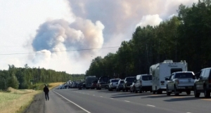 Smoke from the McKinley Fire billows in front of a line of traffic delayed along the Parks Highway.
