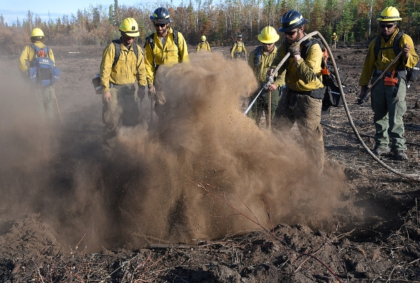 Members of the Missouri_Iowa Coordination Center #3 Type 2 Initial Attack Crew use water to extinguish hot spots they found in peat while cold trailing the Small Timber Fire (#687) of the Chalkyitsik Complex on Sunday, Aug. 4, 2019. The 34-acre fire is holding heat in the deep layers of peat along the Draanjik River due to the extreme drought conditions the area has experienced this season. Sam Harrel/Alaska Interagency Incident Management Team