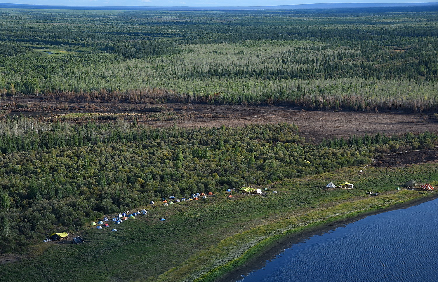 Firefighters' spike camp is set up near the Small Timber Fire (#687) of the Chalkyitsik Complex on Sunday, Aug. 4, 2019. The 34-acre fire is holding heat in the deep layers of peat along the Draanjik River due to the extreme drought conditions the area has experienced this season. Sam Harrel