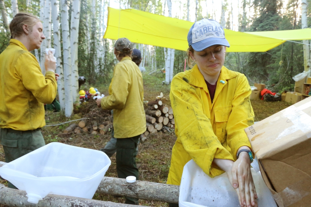 Firefighter Candice Norman washes her hands in a makeshift wash basin made out of an empty cubie on the Zitziana River Fire in June of 2018.