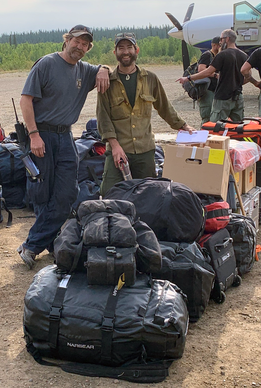 Photo of Colorado Line Medic Ernie Walker and Alaska Fire Medic Evan Sterling and their massive pile of equipment as they wait to demobilize from the Chalkyitsik Complex on Aug. 12, 2019.