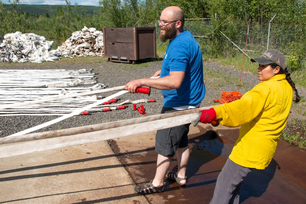 Cache materials handlers Morgan Kotche, on left, and Yolanda Copple move hoses over to be tested for leaks at what is called the hose pond at BLM AFS facilities on Fort Wainwright June 3, 2019. The hose must hold water at 300 psi for three minutes.