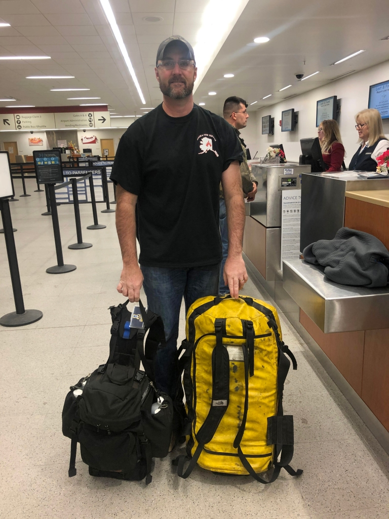 Man standing with his firefighting gear at airport.