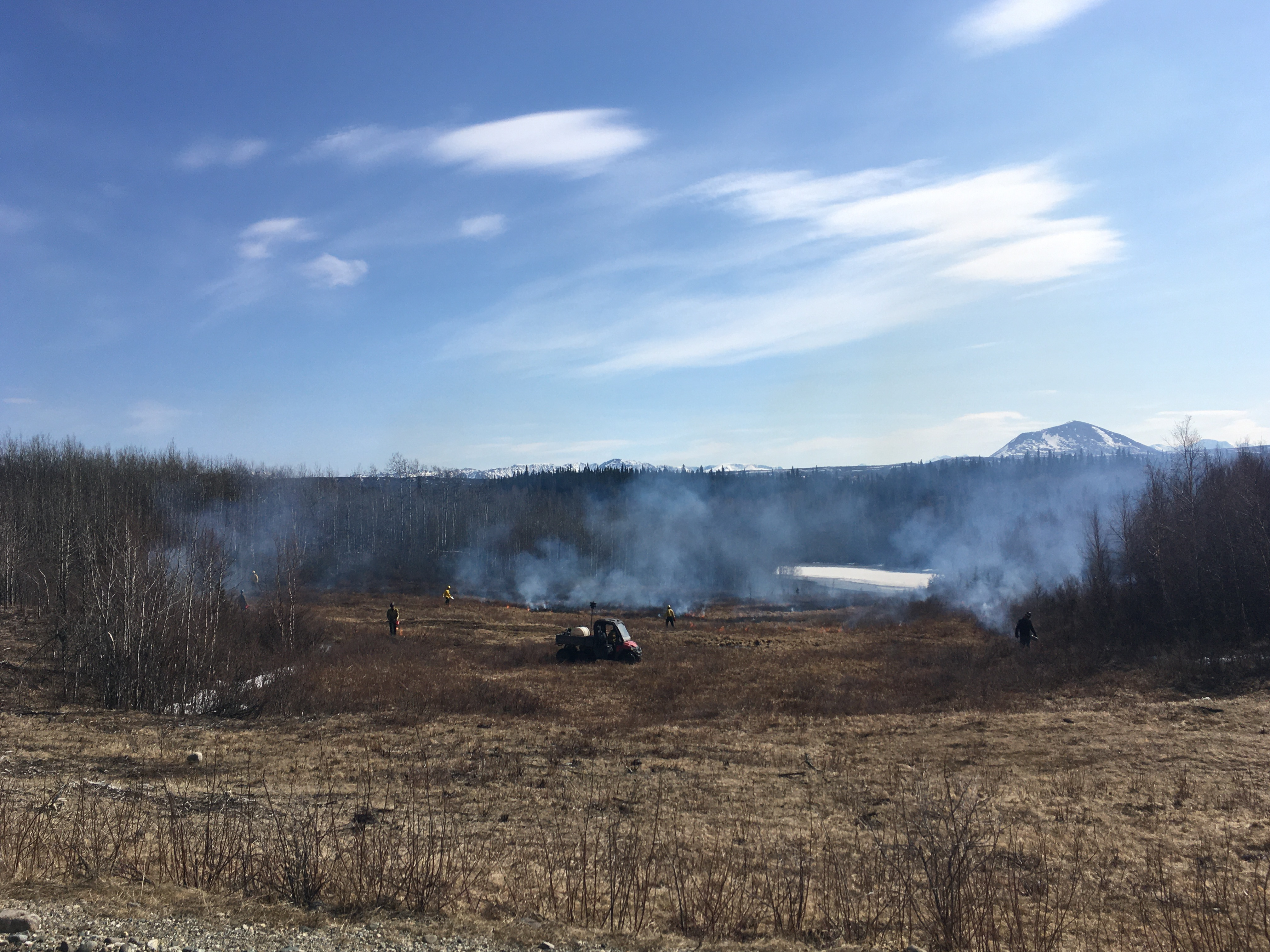 Photos of firefighters in a field with smoke.