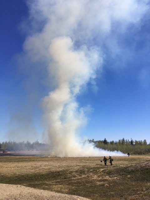 Photo of firefighters and smoke on military training range.
