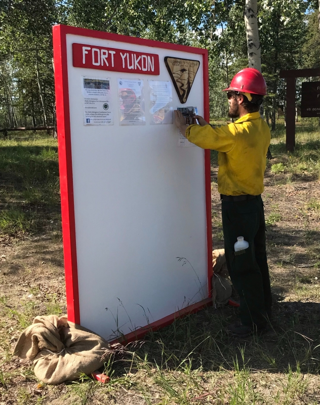 A firefighter stapling updated information on a board.