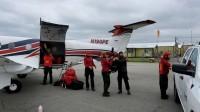 Firefighters loading gear onto plane.