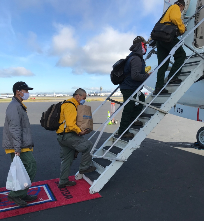 Firefighters boarding a plane.