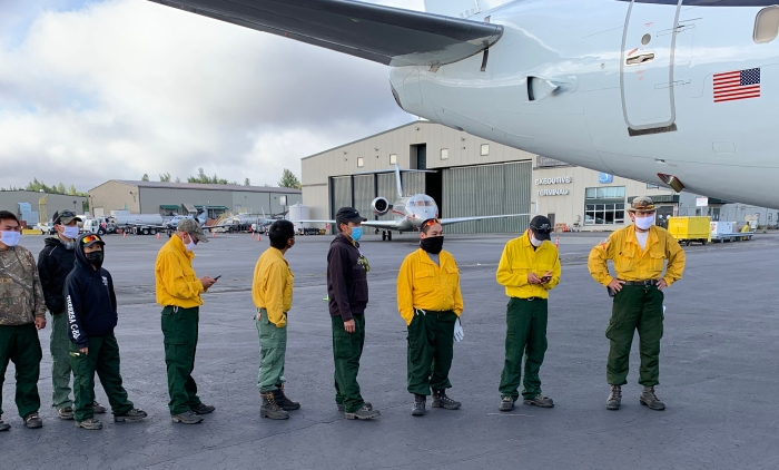 Firefighters wait to board an airplane.