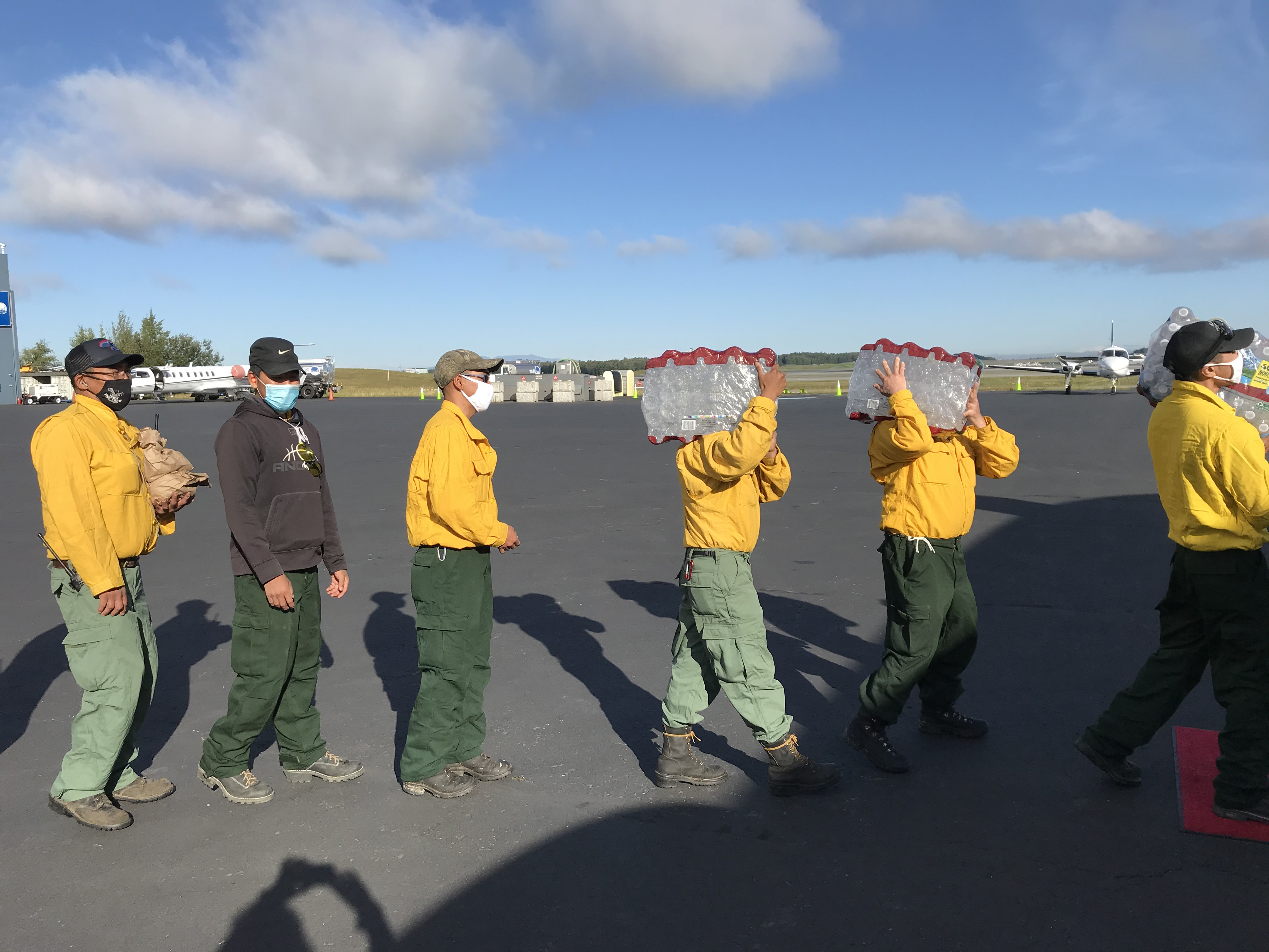 Firefighters in a line on a tarmac.