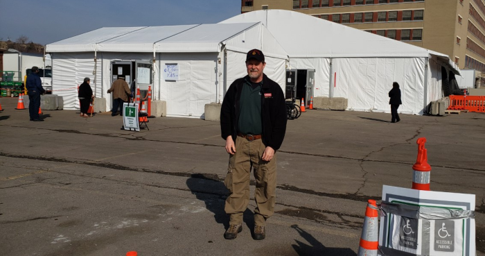 Man standing in front of two large white tents.