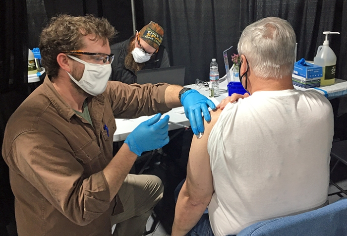 Man giving another man a vaccination in the arm.
