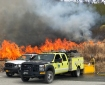 Two fire engines in a parking lot while firefighters burn a field of grass.