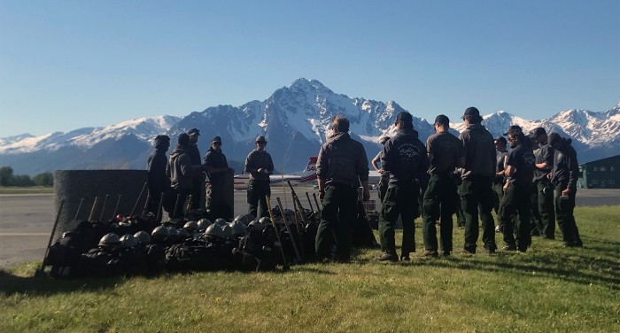Firefighters from the Pioneer Peak Hotshots standing on a runway at Palmer Airport with snow-covered mountains in background.