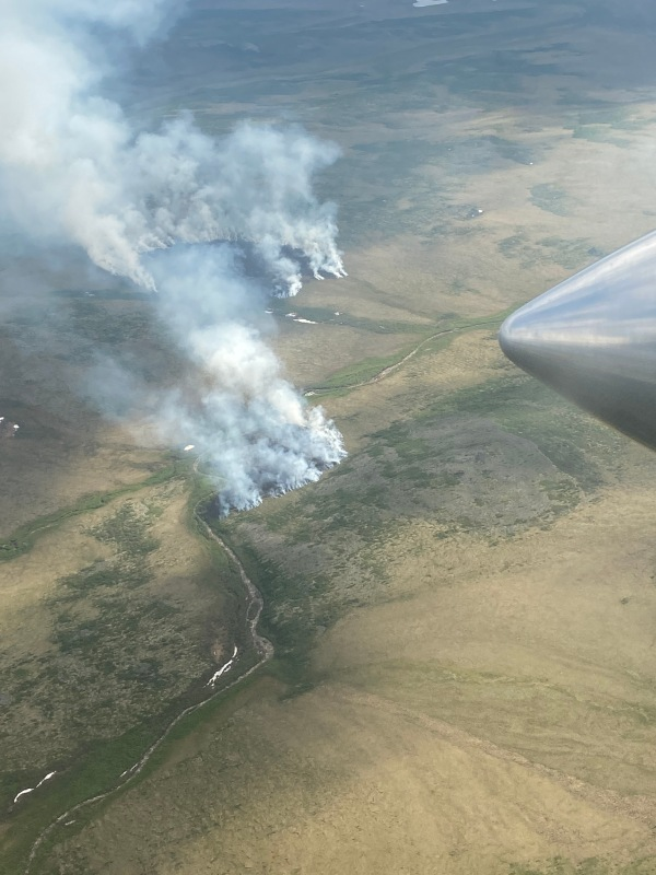 Smoke wafting up from two fires burning in tundra.