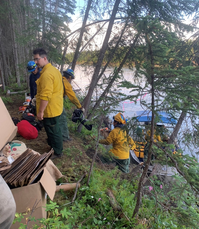 Firefighting personnel on the About Mountain Fire along the Kuskokwim River south of McGrath load supplies into a boat for transport Monday, June 21, 2021.