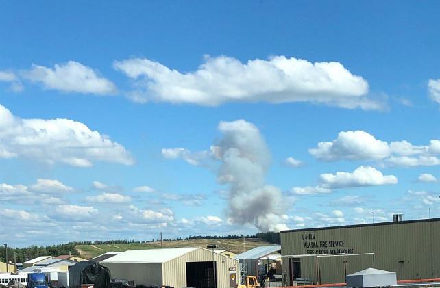 A smoke column rises behind a building.