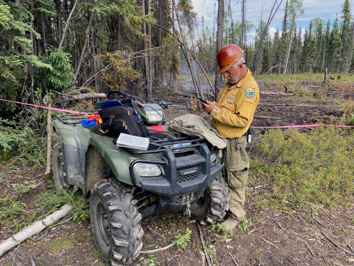 A firefighter standing next to a four-wheeler looking at his phone.