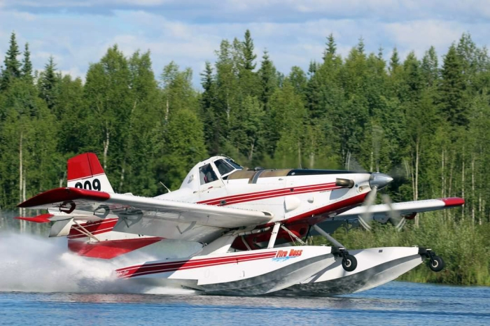 A red and white water-scooping plane dips water from Chena Lakes during initial attack of the Brock Road Fire on Sunday, June 27, 2021.