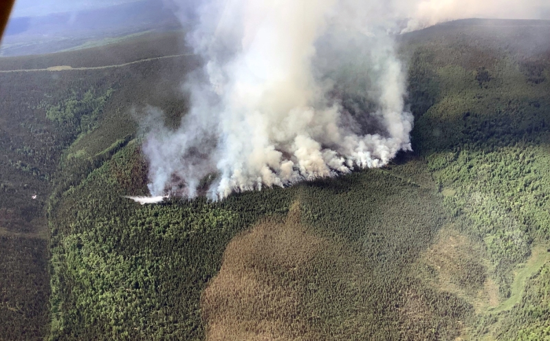 The Haystack Fire burns to the north on Tuesday afternoon, June 15, 2021. A water-scooper can be seen dropping water near the edge of the smoke on the left. Division of Forestry photo