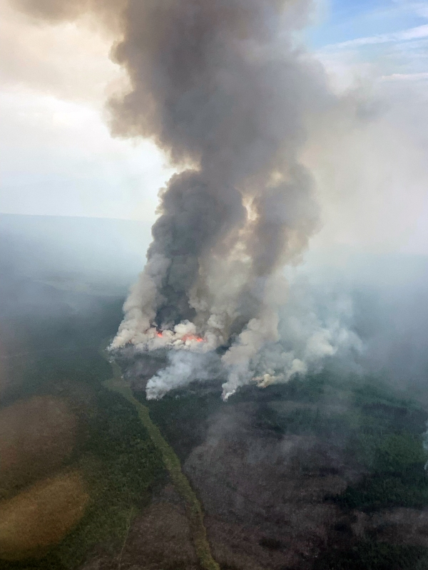 An aerial photo of the Haystack Fire showing a large column of smoke and flames, as well as a fire break cut across the top of the hillside the fire is burning on