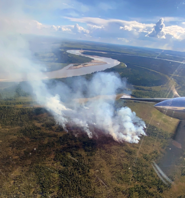 Smoke rising up from a fire with the Tanana River in the background.