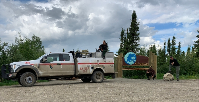 Firefighters with a fire engine at the Arctic Circle Sign on the Dalton Highway.
