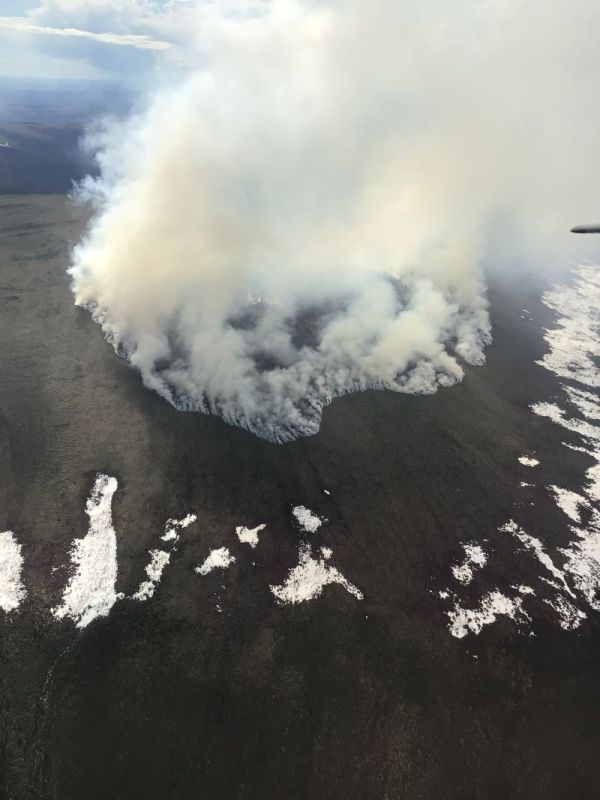 Photo of smoke rising up from tundra interspersed with snow matches.