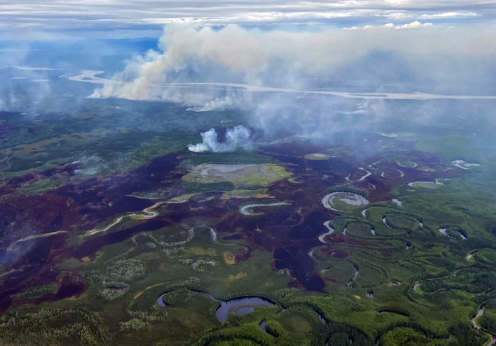 Photo of burned area and smoke burning along a slough pitted landscape.