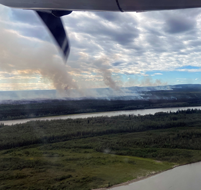 Smoke billowing from a large area near a river.