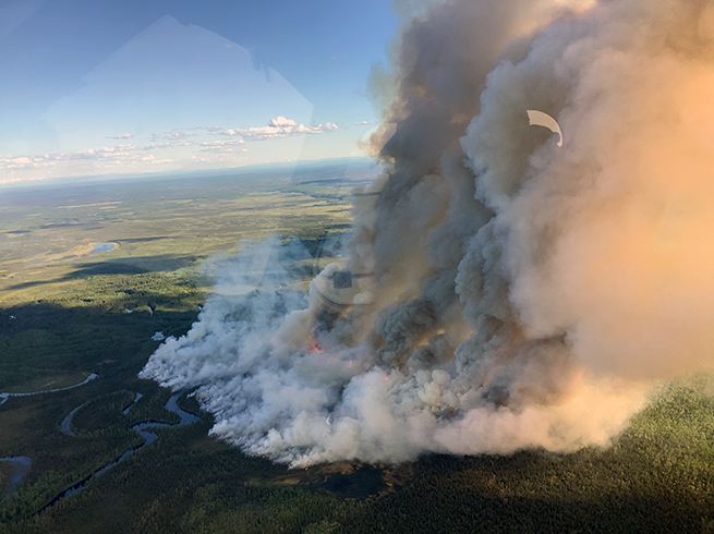 Large column of smoke rising up from burning forest and tundra.