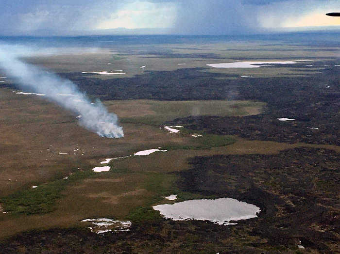 Photo of smoke rising up from tundra next to volcanic rock.