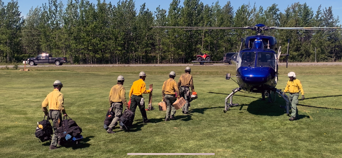 Firefighters walk toward a helicopter to begin loading for a shuttle to the Loon Lake Fire.
