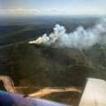 An aerial shot showing a smoke column during initial attack of the 20-acre Winter Trail Fire (#194) burning about 20 miles northeast of Fairbanks near the Fort Knox Gold Mine. The mine road is visible in the bottom fo the photo. Tony Chapman/BLM Alaska Fire Service