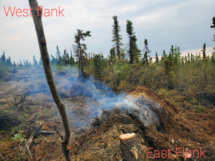 A berm pile smolders along the perimeter of the Haystack Fire