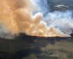 A large column of smoke rising from a wildfire burning through black spruce in the Tetlin National Wildlife Refuge