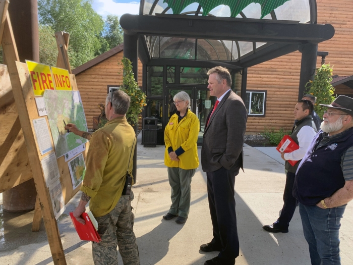 Munson Creek Fire Incident Commander Zane Brown points to a map during a briefing with Gov. Mike Dunleavy and Chena Hot Springs Resort owner Bernie Karl.