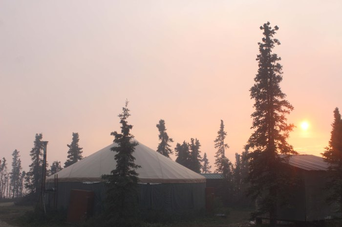 The sun sets behind two aurora viewing yurts above and east of Chena Hot Springs.