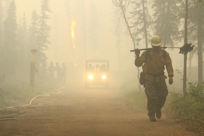 A firefighter walking down a road with an ATV behind him.