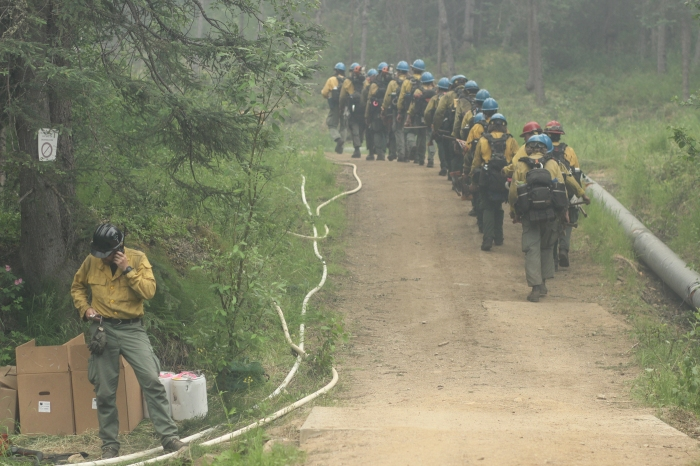 A fire crew marching in single file up a road.