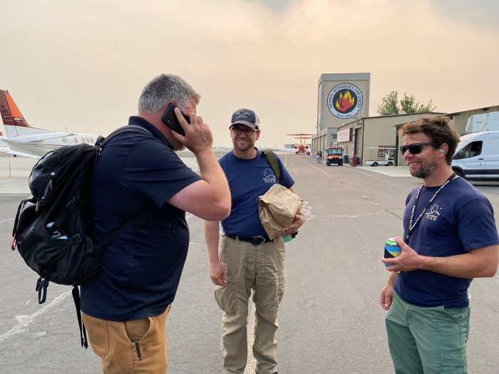 Alaska Type 1 Incident Management Team Commander Norm McDonald of the Alaska Division of Forestry talks on the phone after landing at the National Interagency Fire Center in Boise, Idaho on Tuesday, July 20, 2021. IC trainee Chuck Russell of the National Park Service, middle, and Plans Section Chief Adam Kohley of the BLM Alaska Fire Service look on. Kale Casey/Alaska Incident Management Team.
