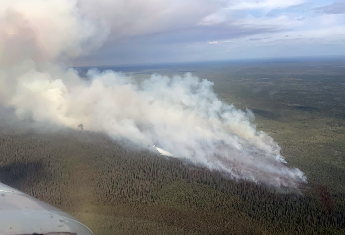 Smoke rising from a wildfire burning in a vast expanse of black spurce.