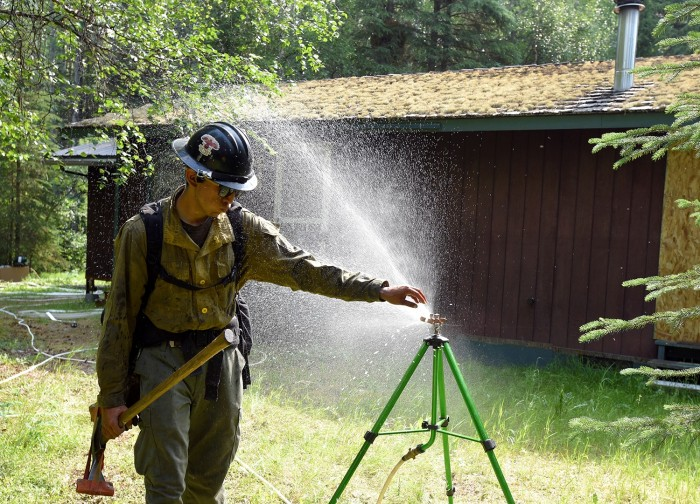 A firefighter sticking his hand in a running sprinkler.